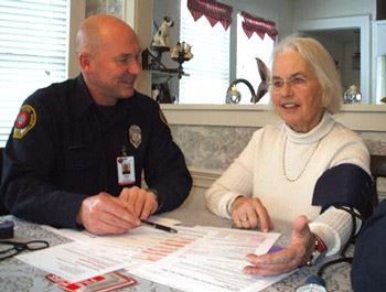 Firefighter Visiting With Older Woman